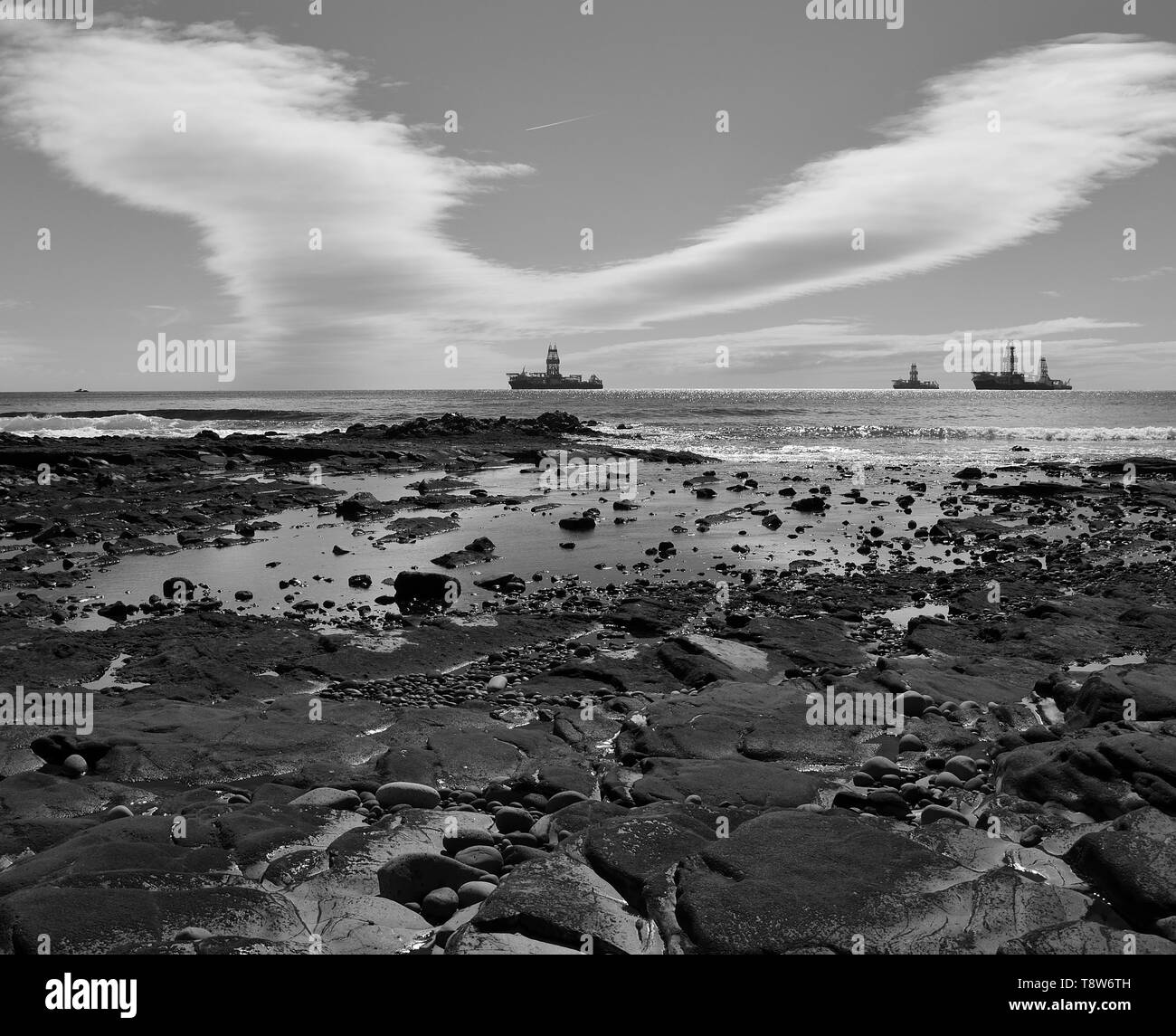 Coast landscape at low tide, oil rigs and cloudy sky, black and white, bay of Las Palmas, Gran Canaria - Stock Image