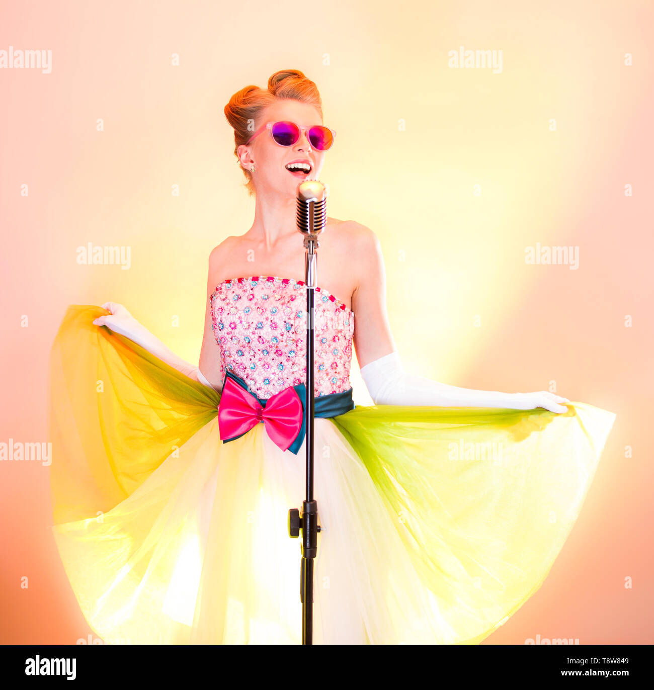 Happy girl singer in pink glasses smiles, flirts, enjoys life, dances, have fun, sings into silver retro microphone. Stylish teenager musician in - Stock Image
