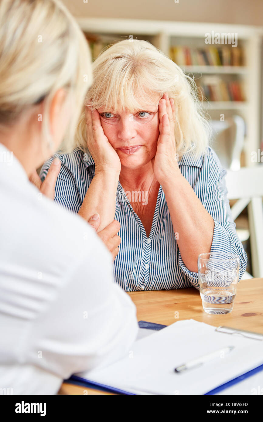 Doctor or nursing consoling caring senior woman with sorrow and worries - Stock Image