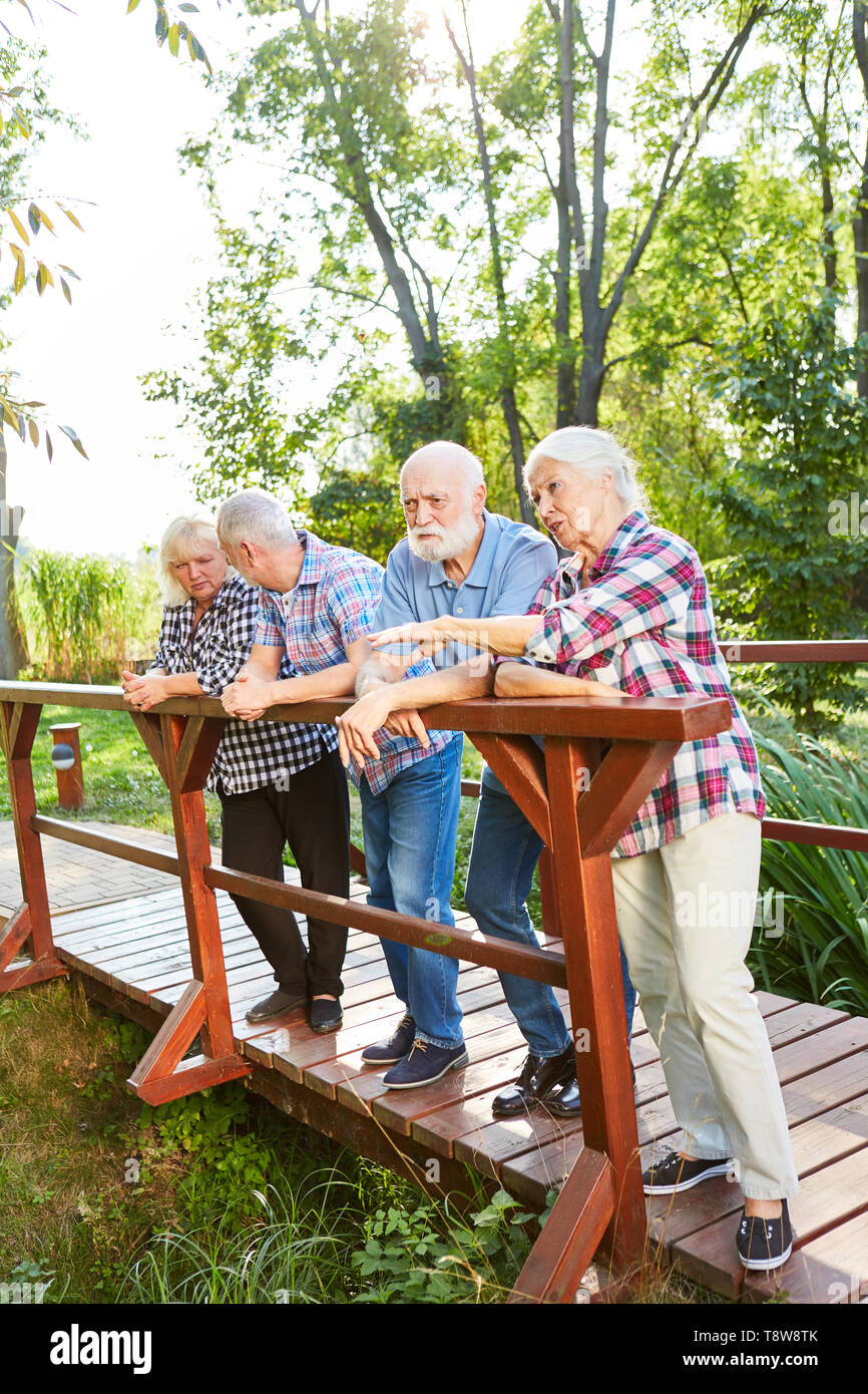 Group of seniors stands relaxed on a wooden bridge on a hike - Stock Image