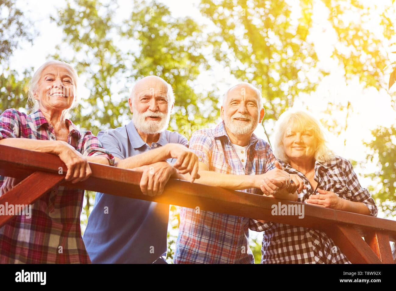Group of seniors taking a break while hiking in the summer - Stock Image