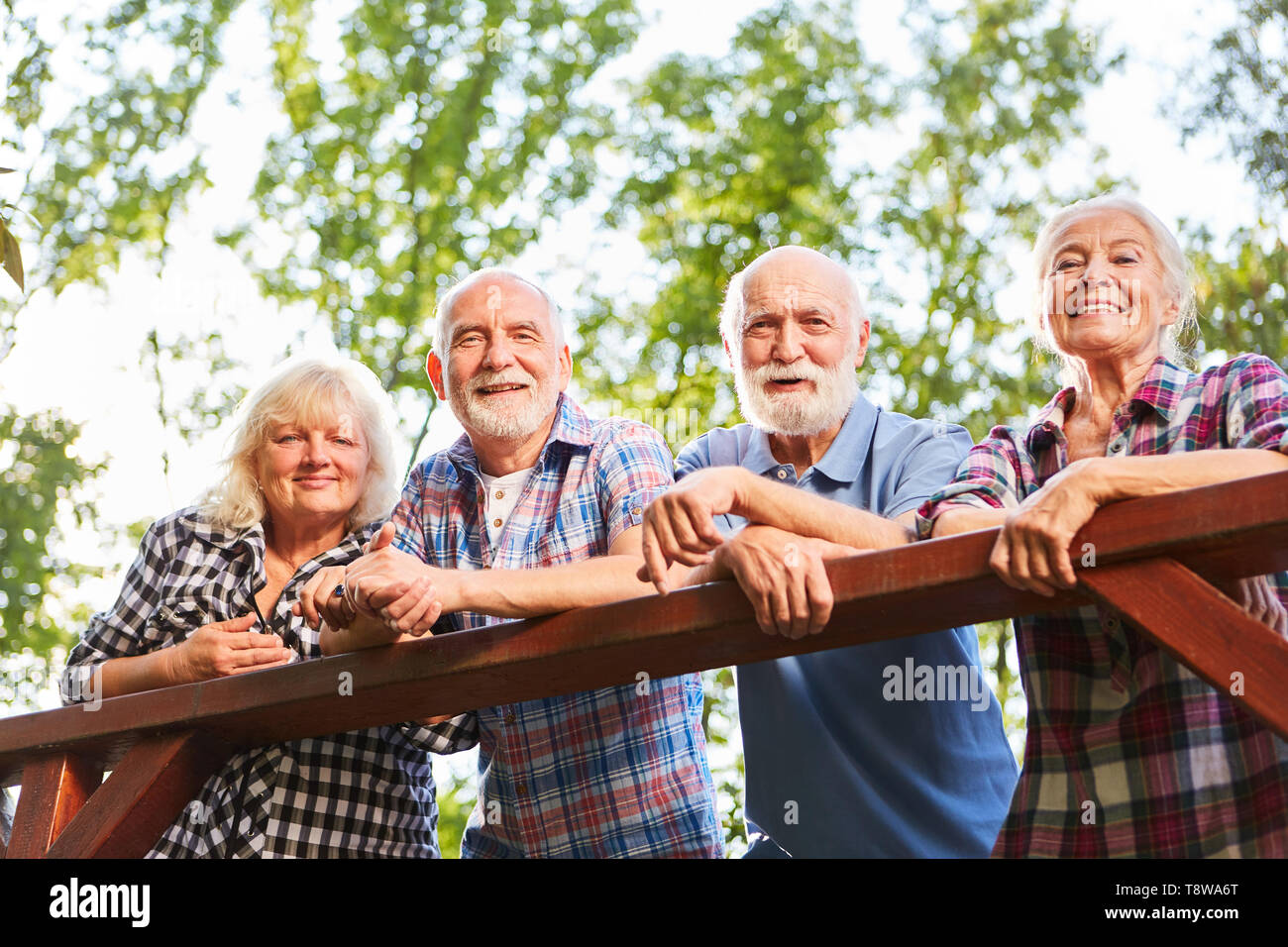Seniors as friends are leaning against a bridge railing on a tour - Stock Image
