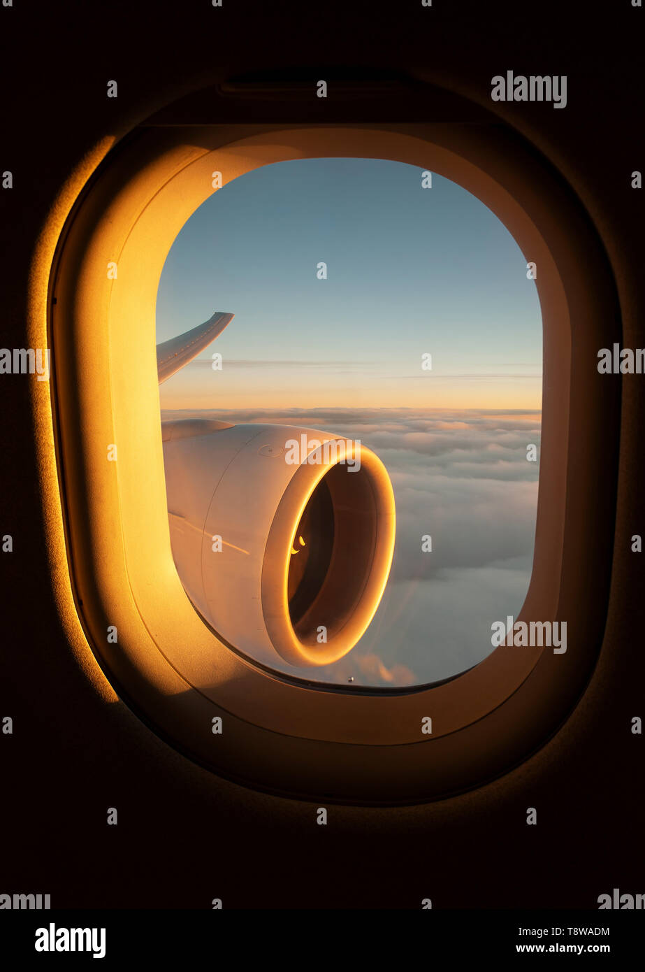 View out of an airplane window of the jet's wing and engine whilst the sun sets Stock Photo