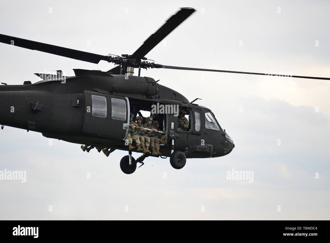 U.S. Army Paratroopers assigned to 54th Brigade Engineer Battalion, 173rd Airborne Brigade, on board from a 12th Combat Aviation Brigade UH-60 Black Hawk helicopter, at Juliet Drop Zone, Pordenone, Italy, during airborne operation, May 9, 2019. The 173rd Airborne Brigade is the U.S. Army's Contingency Response Force in Europe, capable of projecting ready forces anywhere in the U.S. European, Africa or Central Commands' areas of responsibility. (U.S. Army's Photos by Paolo Bovo) - Stock Image