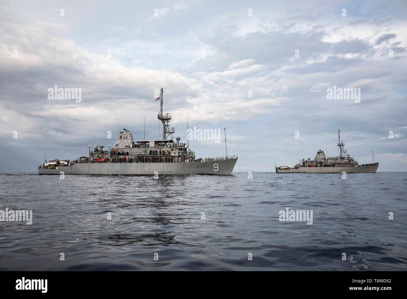 190508-N-AD347-1105 SOUTH CHINA SEA (May 8, 2019) Sailors pose for a photo on the weather decks of the Avenger-class mine countermeasures ship USS Pioneer (MCM 9) and her sister ship USS Patriot (MCM 7) while underway. Both Pioneer and Patriot, part of Mine Countermeasures Squadron 7, are operating in the U.S. 7th Fleet area of operations to enhance interoperability with partners and serve as a ready-response platform for contingency operations. (U.S. Navy photo by Lt. j.g. Alexander Fairbanks) - Stock Image