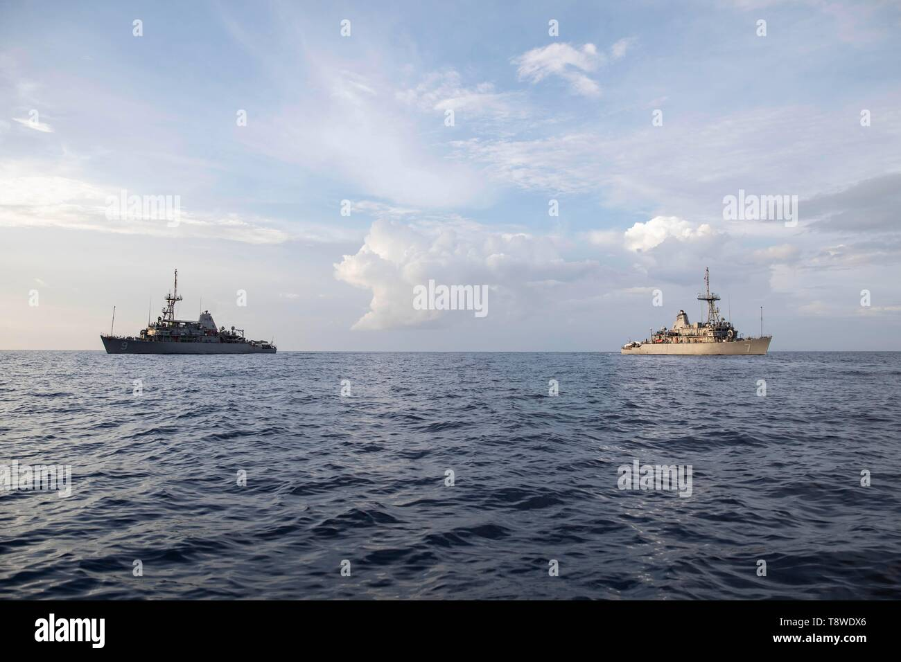 190508-N-AD347-1245 SOUTH CHINA SEA (May 8, 2019) The Avenger-class mine countermeasures ship USS Pioneer (MCM 9) and her sister ship USS Patriot (MCM 7) underway. Both Pioneer and Patriot, part of Mine Countermeasures Squadron 7, are operating in the U.S. 7th Fleet area of operations to enhance interoperability with partners and serve as a ready-response platform for contingency operations. (U.S. Navy photo by Lt. j.g. Alexander Fairbanks) - Stock Image