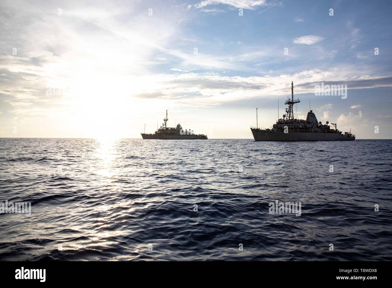 190508-N-AD347-1185 SOUTH CHINA SEA (May 8, 2019) The Avenger-class mine mine countermeasures ship USS Pioneer (MCM 9) and her sister ship USS Patriot (MCM 7) underway. Both Pioneer and Patriot, part of Mine Countermeasures Squadron 7, are operating in the U.S. 7th Fleet area of operations to enhance interoperability with partners and serve as a ready-response platform for contingency operations. (U.S. Navy photo by Lt. j.g. Alexander Fairbanks) - Stock Image