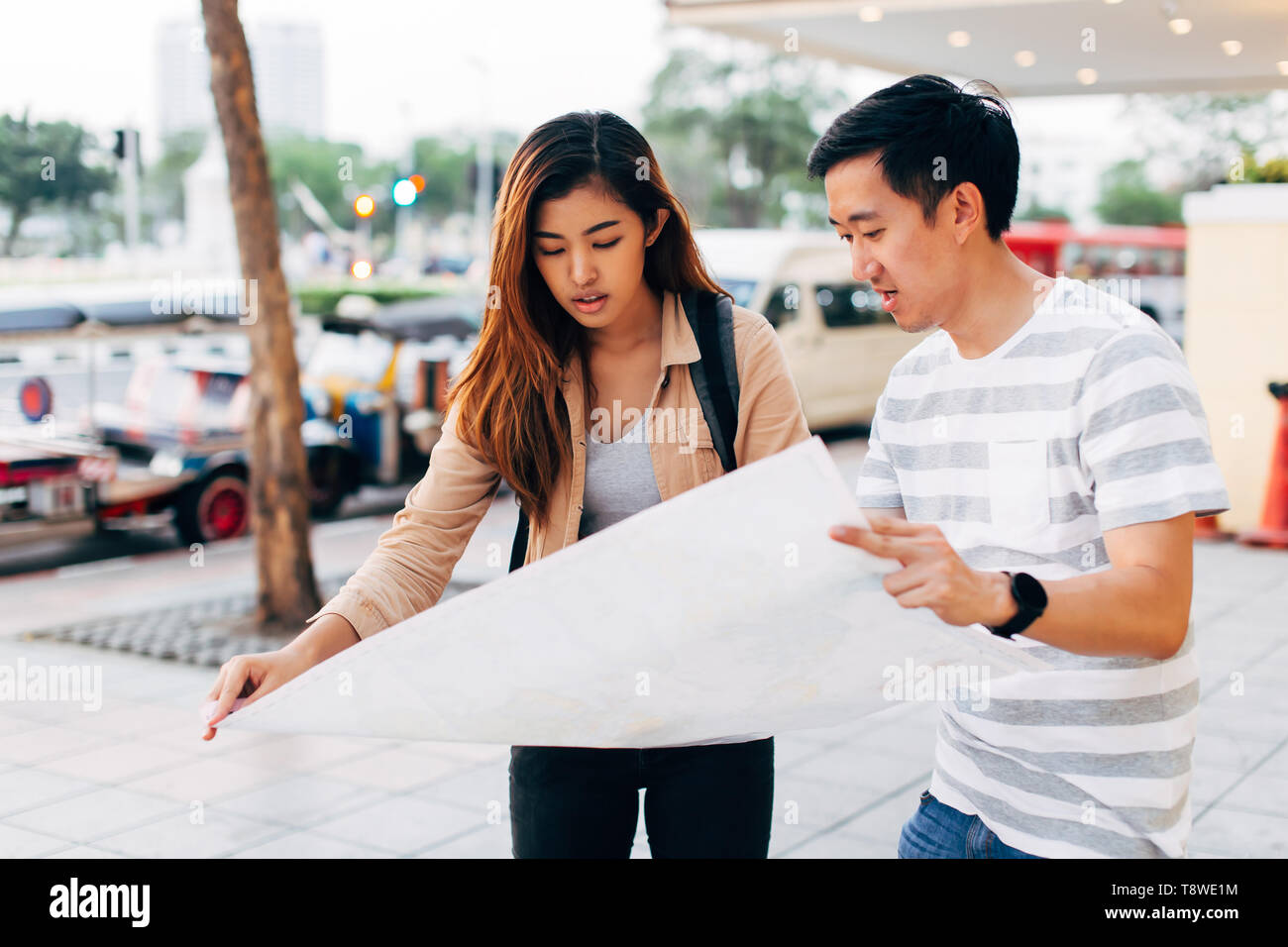 Traveling Asian woman and man reading map on street of Bangkok exploring city together, Thailand - Stock Image