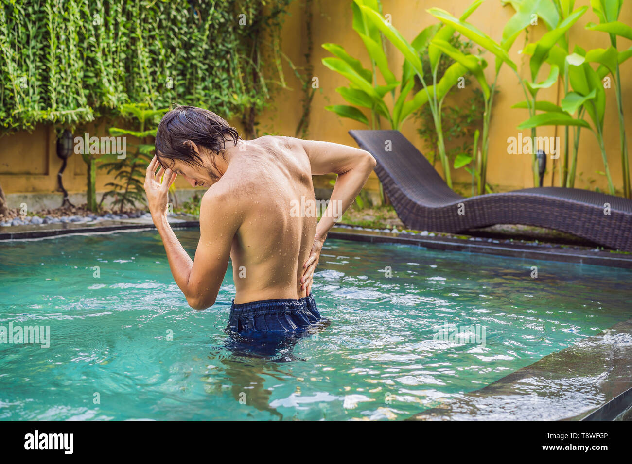 Men's back hurts against the backdrop of the pool. Pool helps with back pain - Stock Image