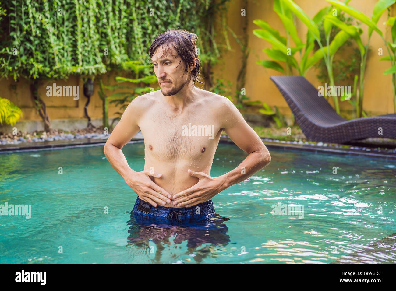 The man's stomach hurts after the pool - Stock Image