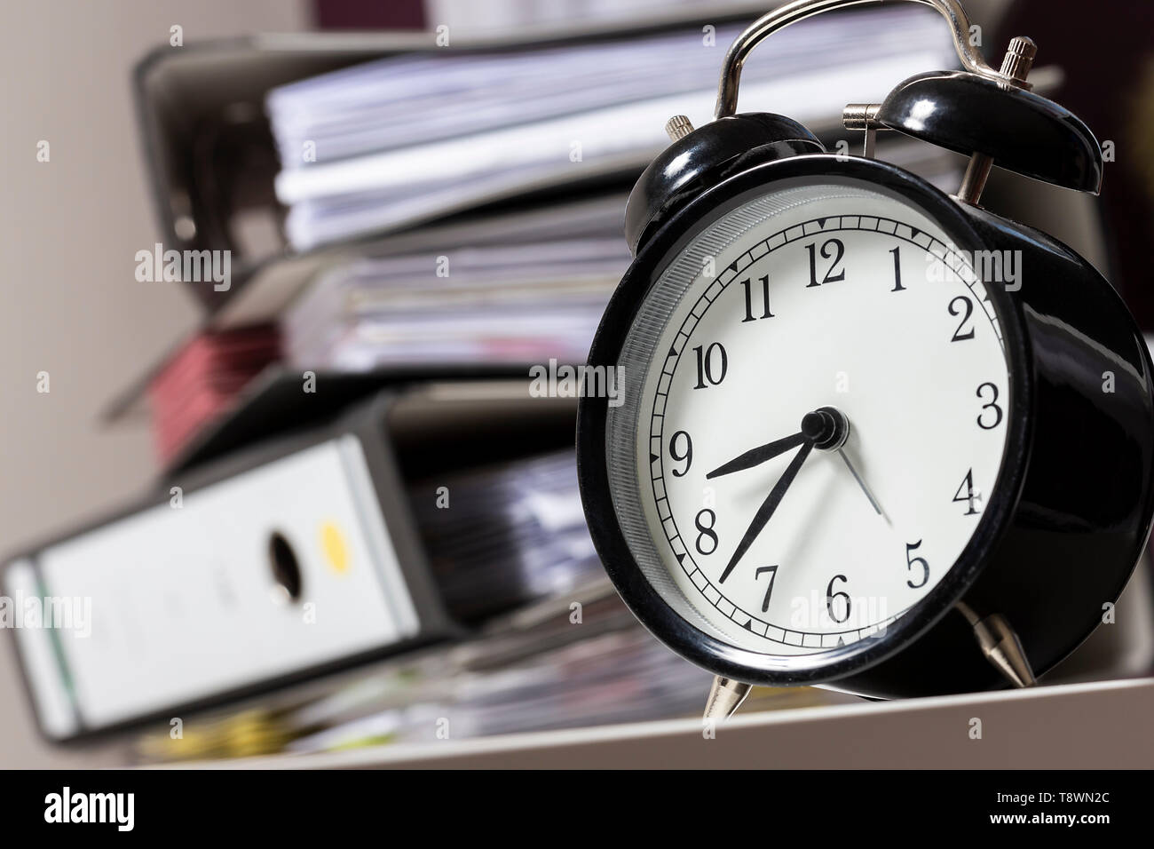 Alarm clock in an office next to a pile of files - Stock Image