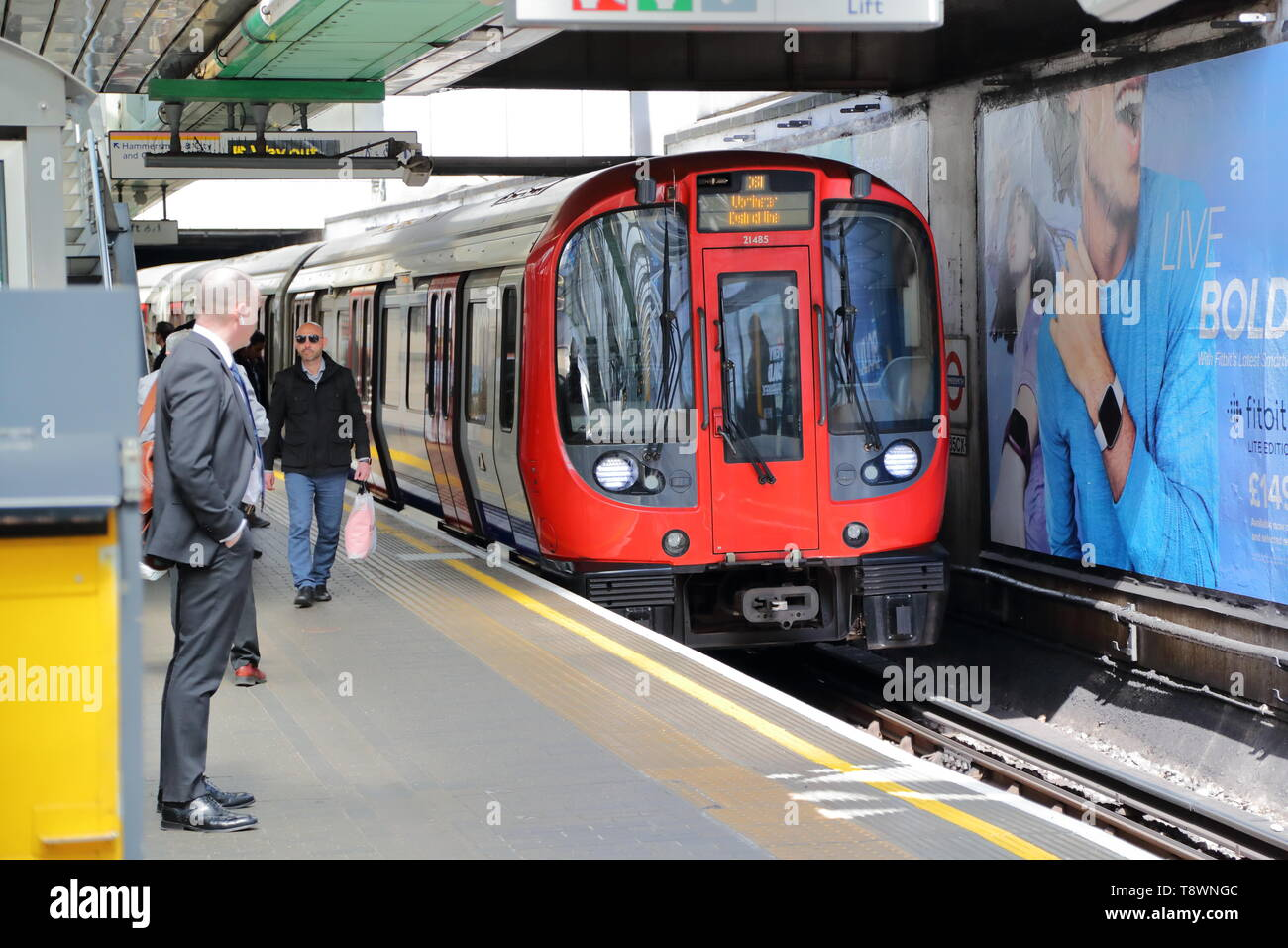 An Underground train arriving at Hammersmith tube station, London, UK - Stock Image