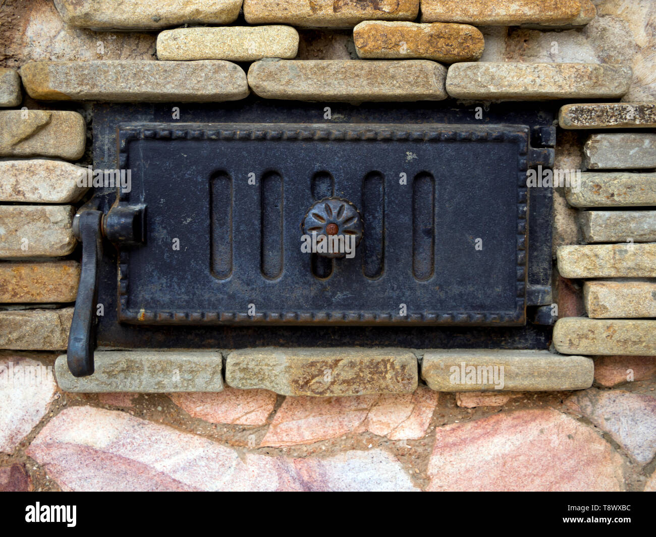 Blown stone stove with a decorative cast iron door - Stock Image