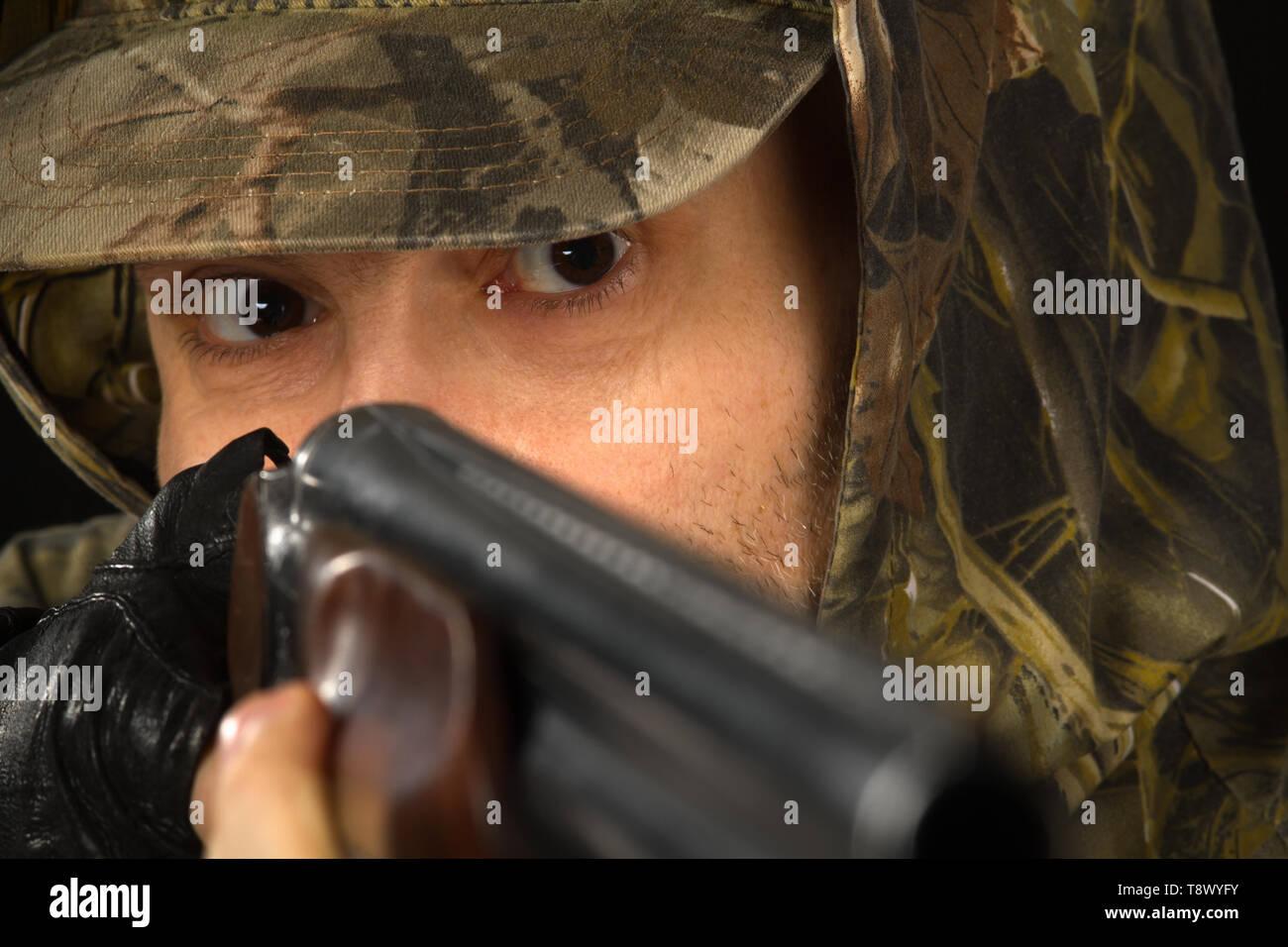 eyes of a hunter aiming with a shotgun, closeup - Stock Image