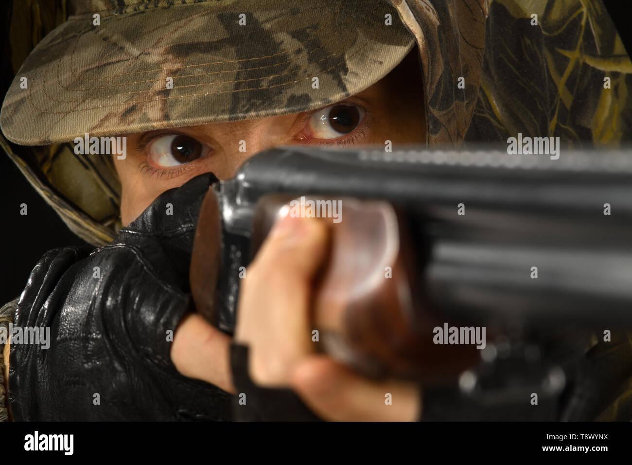 the face of a hunter aiming a shotgun, closeup - Stock Image