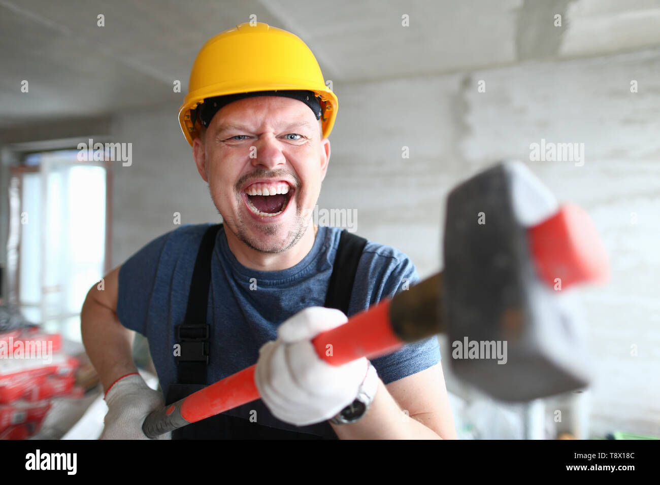 Angry builder holding sledgehammer and Stock Photo