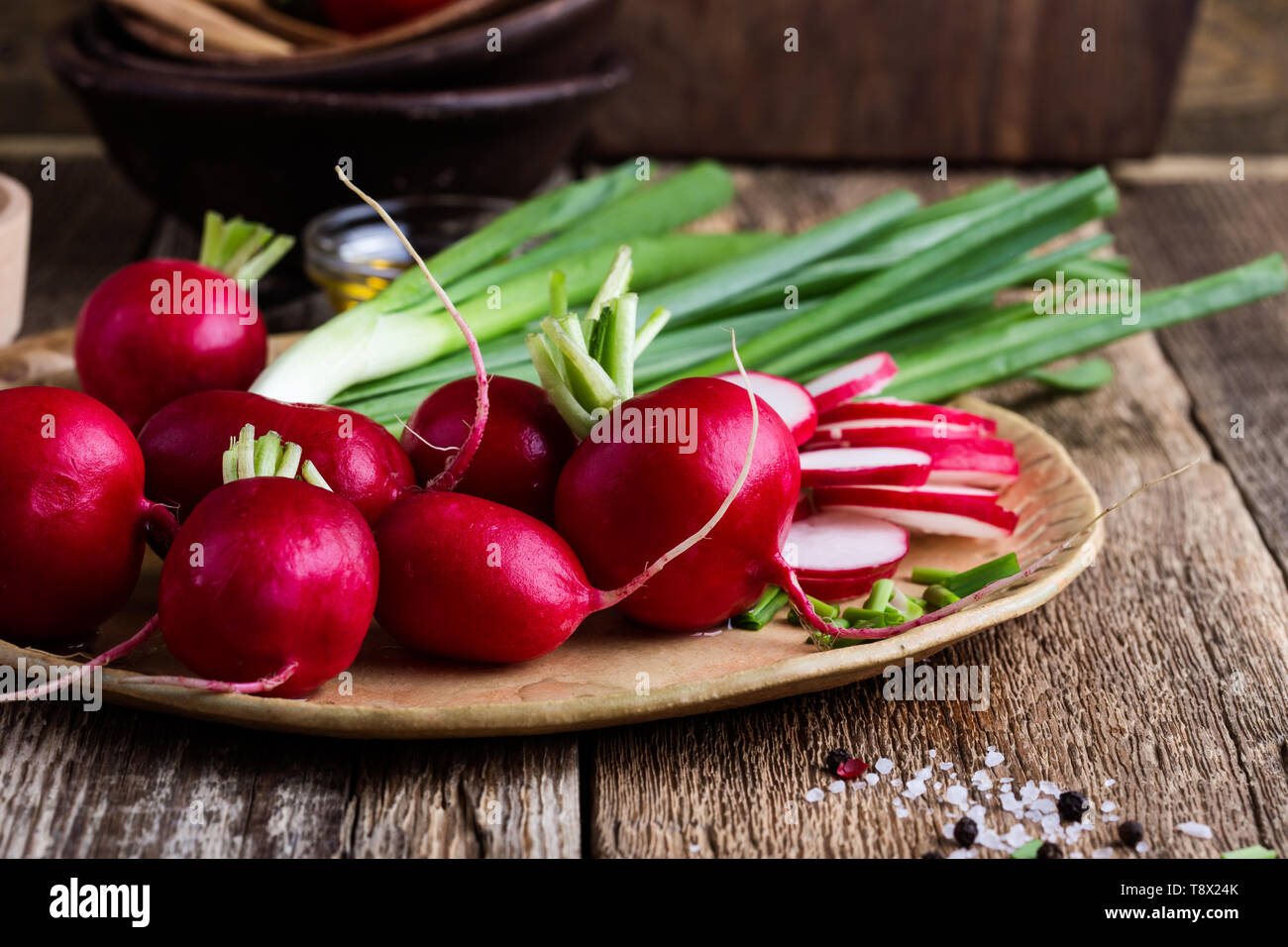 Fresh springtime radishes, green onion and garlic on rustic wooden background, plant based food cooking  ingredients, close up, selective focus Stock Photo