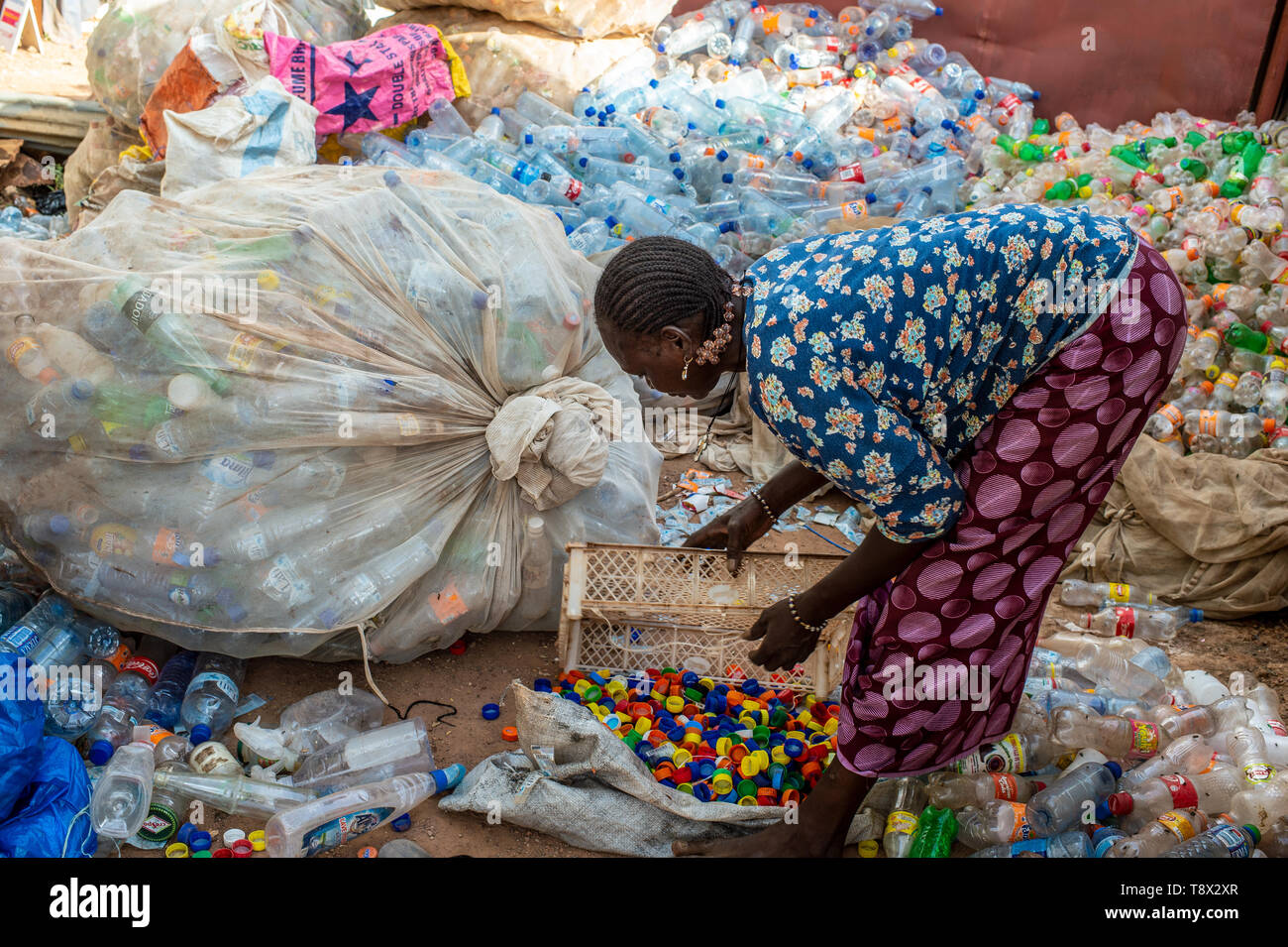 Woman collects and recycles plastic bottles in the Boinsyaaré market, in the Burkina Faso capital Ouagadougou, Africa. - Stock Image
