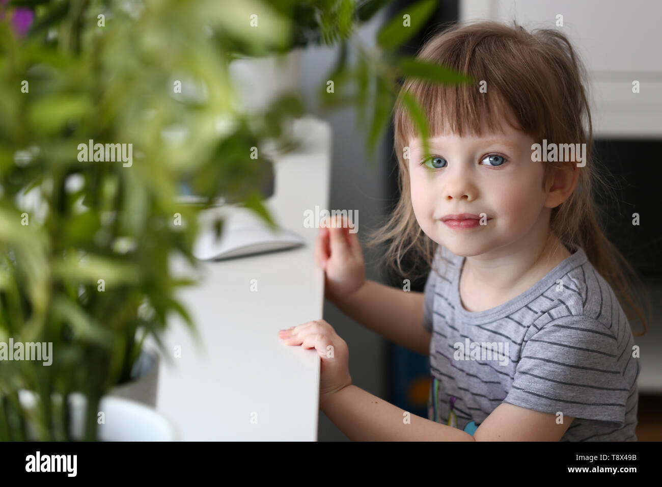 Happy little girl sitting at table looking into - Stock Image
