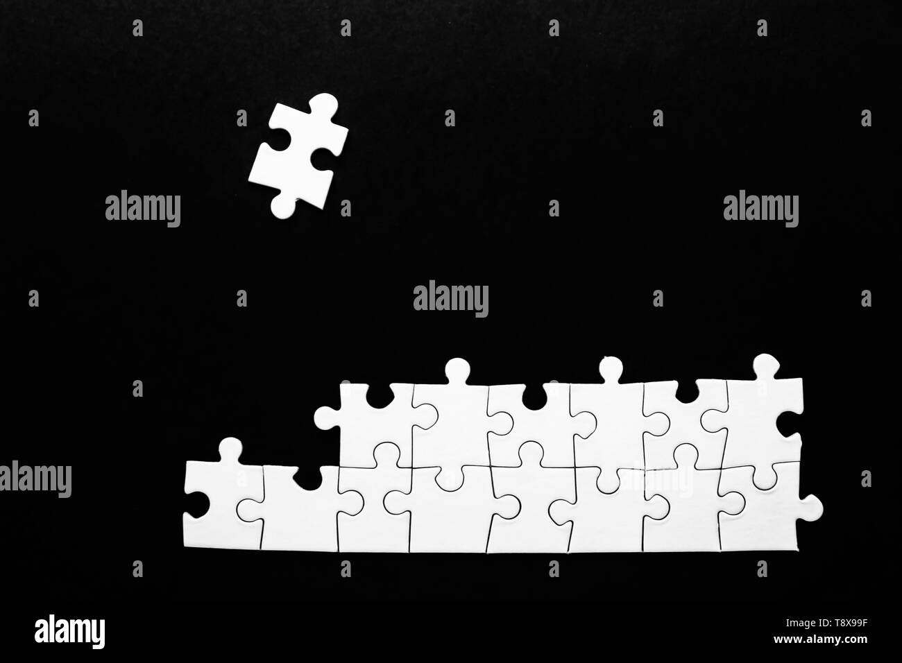Incomplete jigsaw puzzle on dark background - Stock Image