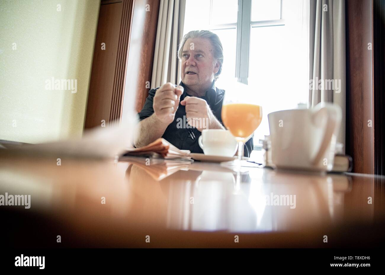Berlin, Germany. 15th May, 2019. Steve Bannon, former advisor to the US president and US publicist, sits on a chair in a room of the Hotel Adlon during an interview with the German press agency dpa and gestures. Credit: Kay Nietfeld/dpa/Alamy Live News - Stock Image