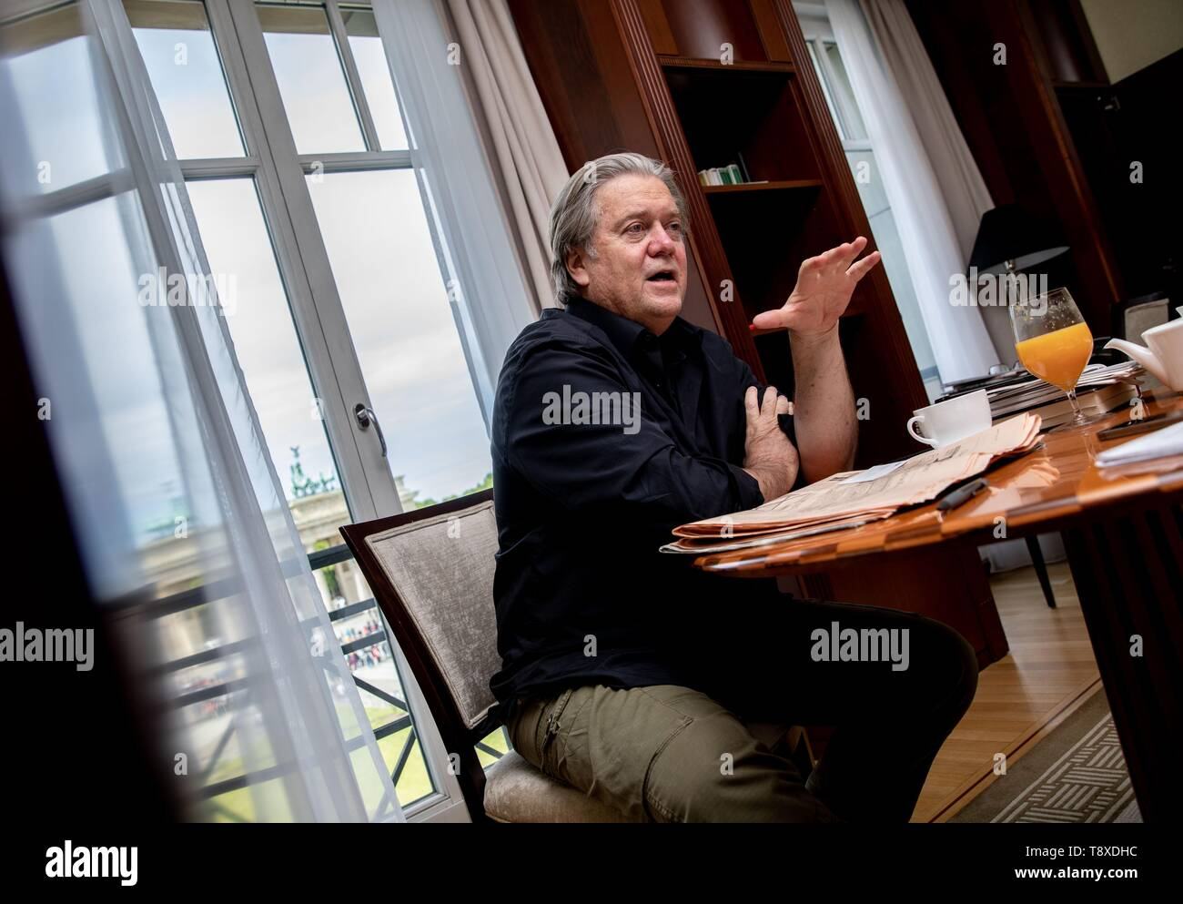 Berlin, Germany. 15th May, 2019. Steve Bannon, former advisor to the US president and US publicist, sits on a chair in a room of the Hotel Adlon during an interview with the German Press Agency dpa with a view of the Brandenburg Gate and gestures. Credit: Kay Nietfeld/dpa/Alamy Live News - Stock Image