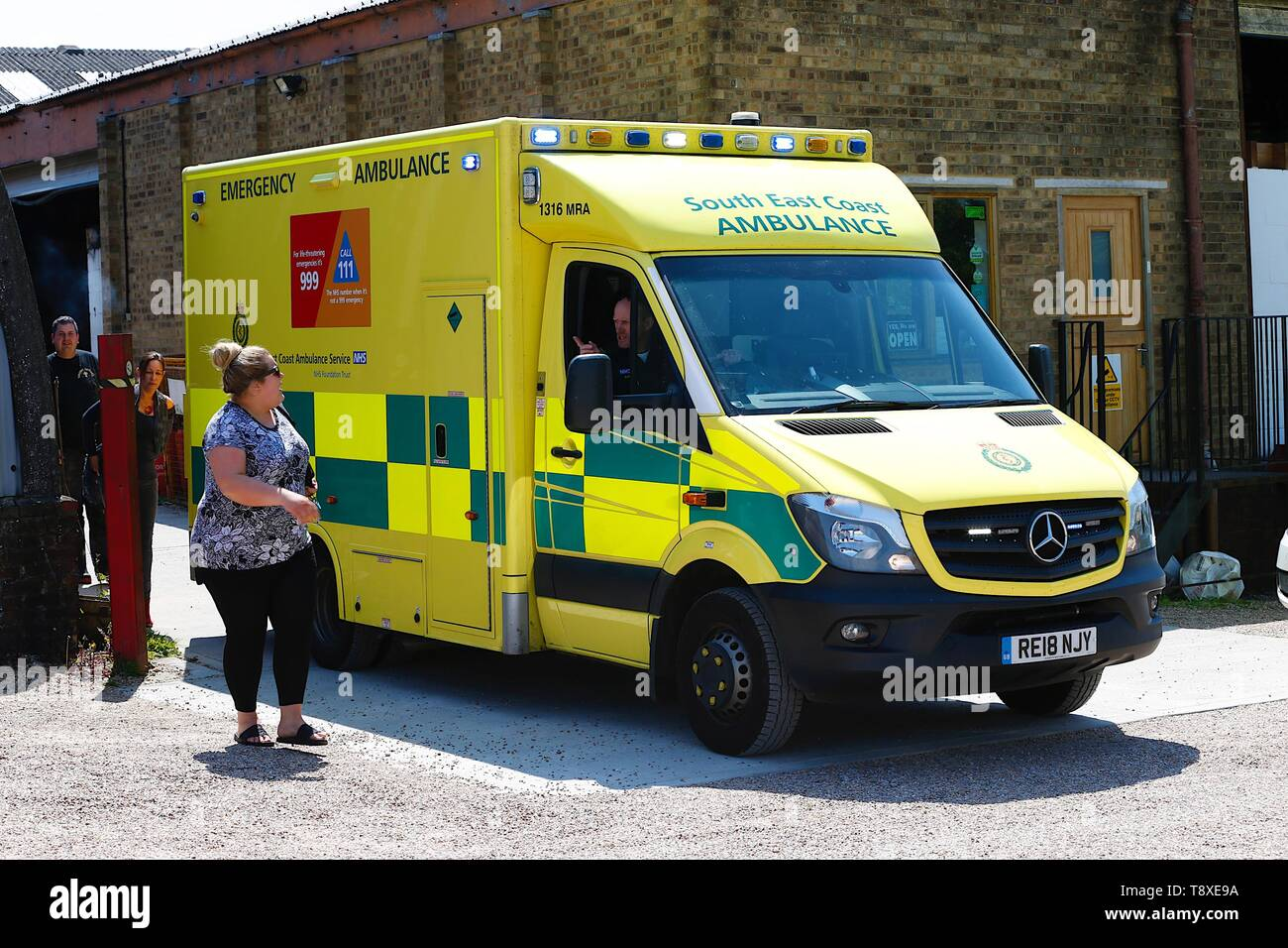 Tenterden, Kent, UK. 15th May, 2019. A Kent Surrey Sussex air ambulance as been dispatched to an incident in the town centre. Medical staff are at scene. The emergency has taken place at the Old Dairy Brewery in the town centre. The driver of a South East Coast ambulance talks to a relative at the scene of the accident. Credit: Paul Lawrenson 2019, Photo Credit: Paul Lawrenson/Alamy Live News - Stock Image
