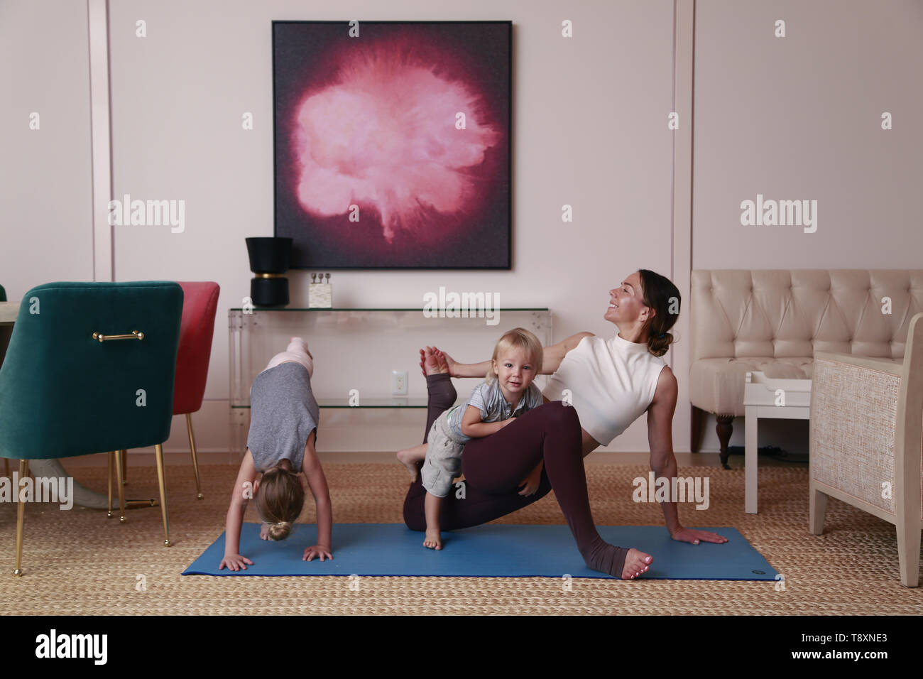 San Diego, CALIFORNIA, USA. 9th Nov, 2018. November 9, 2018 - San Diego, California, USA - A woman does yoga in a home with her two small children. Credit: KC Alfred/ZUMA Wire/Alamy Live News - Stock Image