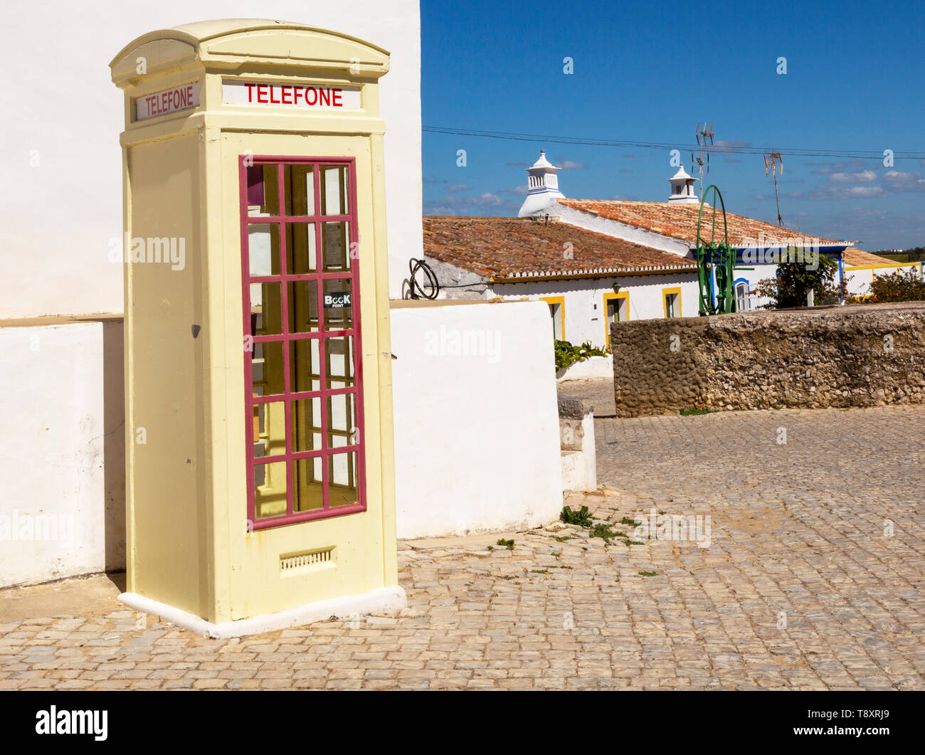 Old fashioned Telephone Telefone box kiosk in street of traditional Portuguese village, Cacela Velha, Algarve, Portugal, Southern Europe - Stock Image