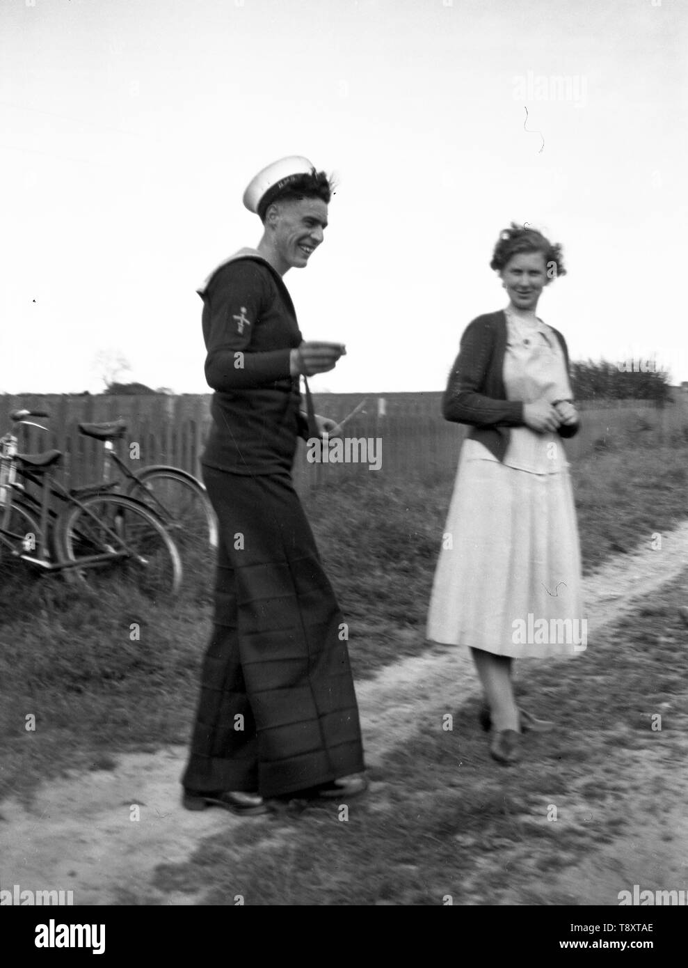 A candid image of a British Sailor in uniform on leave with a woman. Note the bell bottom trousers. c1930 Photo by Tony Henshaw - Stock Image