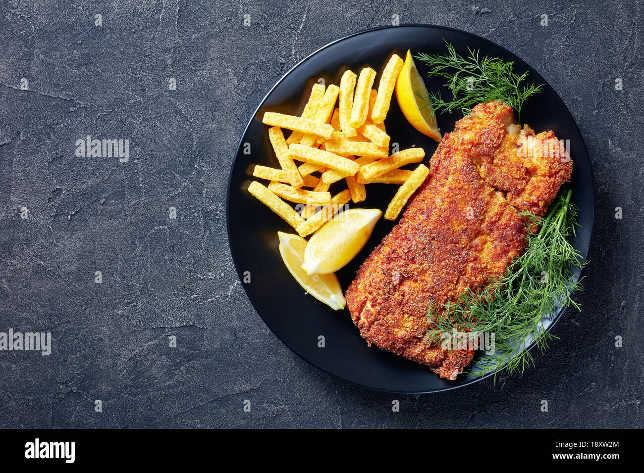 Breaded hake fillet served on a black plate with chips, fresh dill and lemon slices, view from above, flatlay, copy space - Stock Image