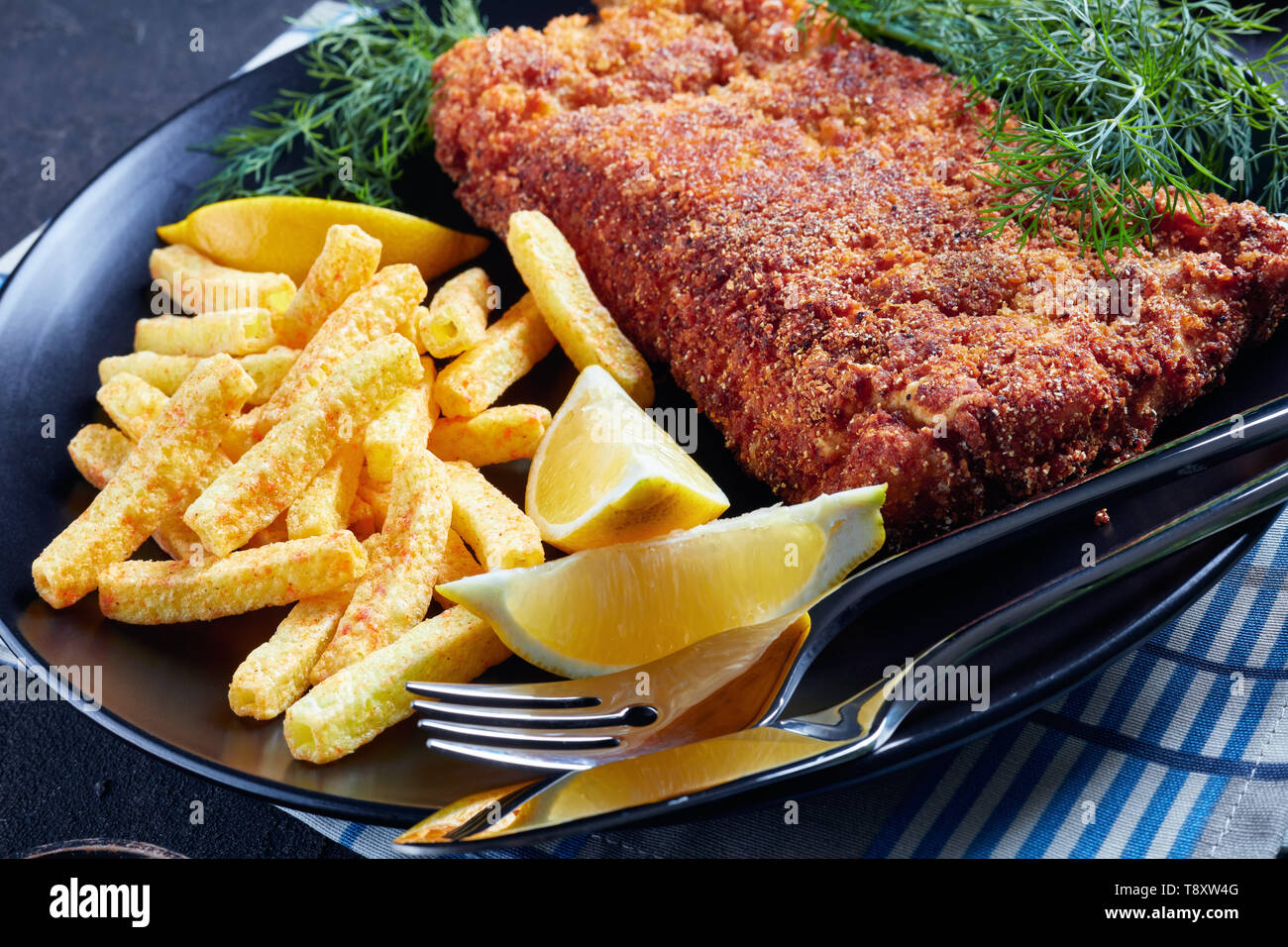 close-up of Breaded hake fillet served with chips, fresh dill and lemon slices on a black plate on a concrete table, top view - Stock Image