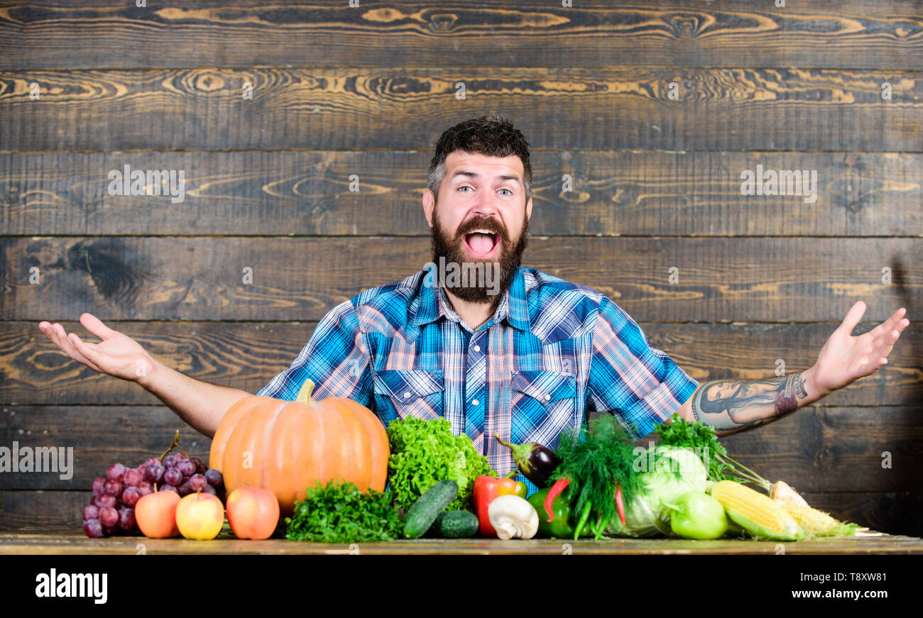 Vegetables organic harvest. Farmer rustic style guy. Vegetarian lifestyle concept. Natural foods. Man bearded farmer harvest wooden background. Welcome to my farm. Farmer with homegrown vegetables. - Stock Image
