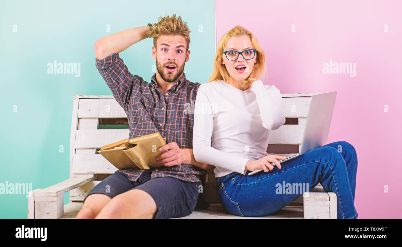 Students preparing for entrance exam. Couple students with book and laptop studying. Man and woman realised that are not ready for passing exam, scared to fail test. Couple shocked because of exam. - Stock Image