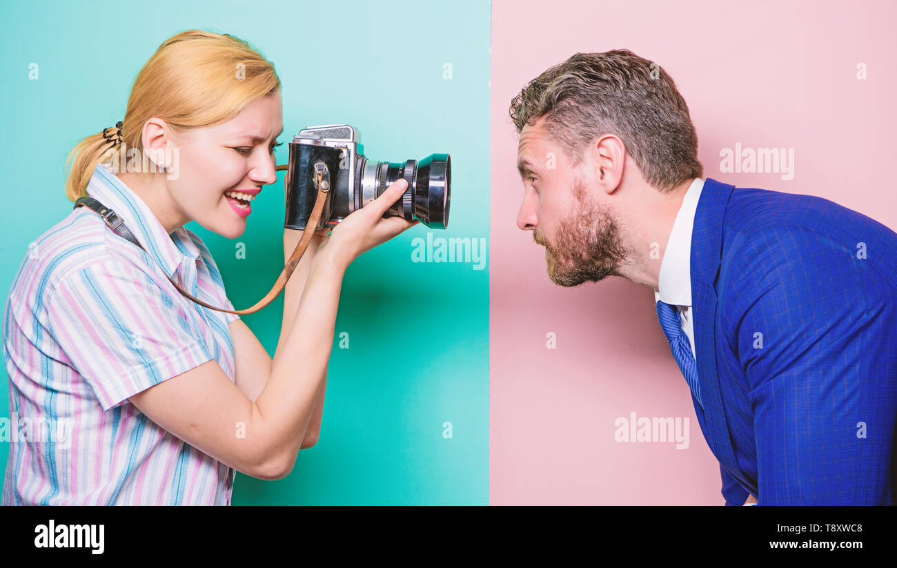 He is photogenic. Pretty woman using professional camera. Businessman posing in front of female photographer. Photographer shooting male model in studio. Fashion shooting in photo studio. - Stock Image
