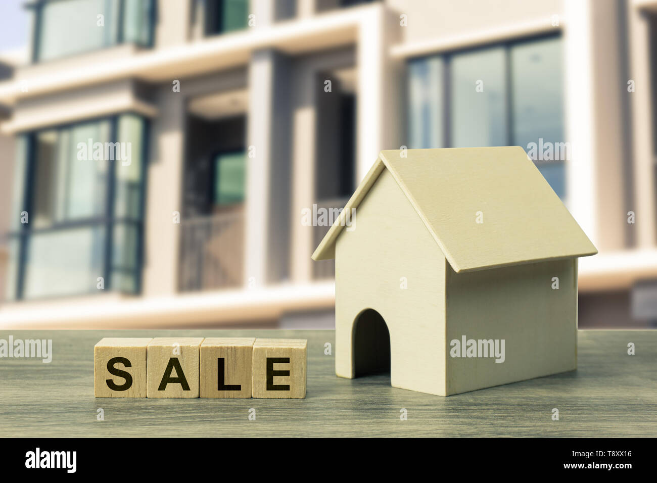 Home and real estate sale concept. A small residential model with sale wooden block on wood table on blurred real estate as background. Depicts house  - Stock Image