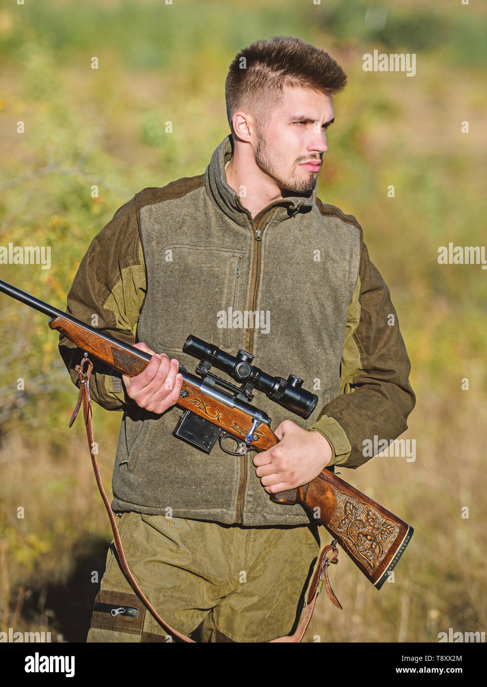 Hunting and trapping seasons. Bearded serious hunter spend leisure hunting. Man brutal unshaved gamekeeper nature background. Hunting permit. Hunter hold rifle. Hunting is brutal masculine hobby. - Stock Image