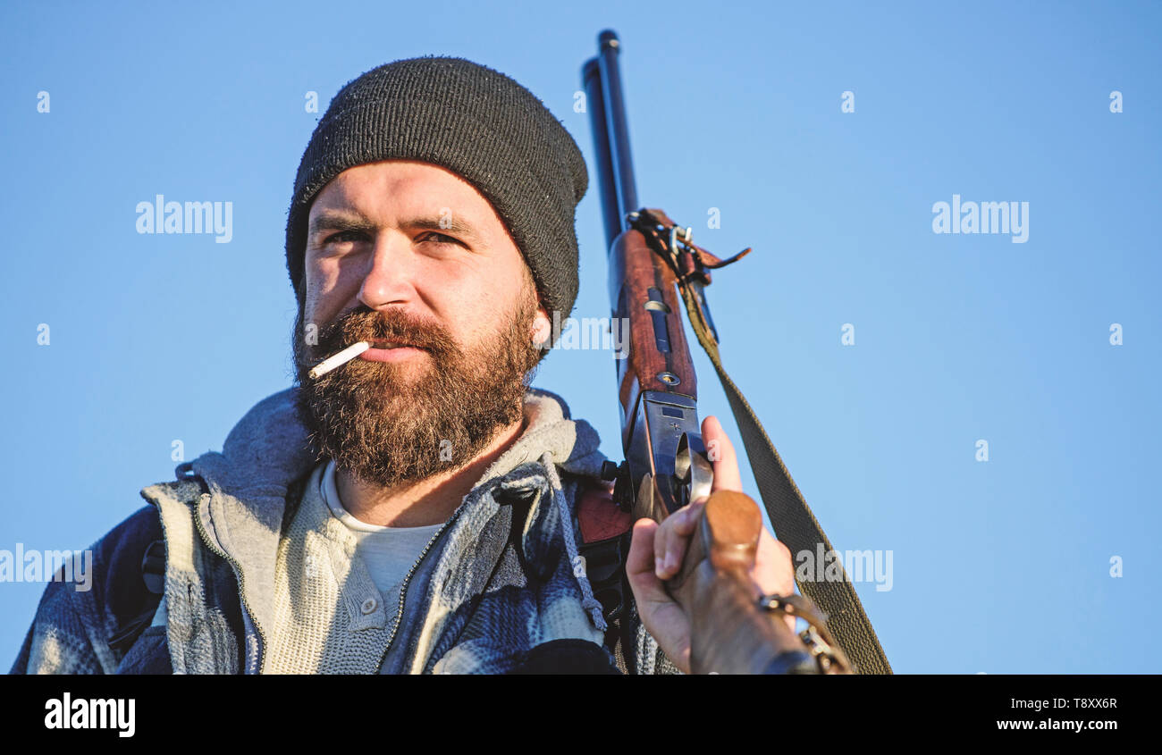 Hunting masculine hobby concept. Man brutal bearded guy gamekeeper blue sky background. Brutality and masculinity. Hunter with rifle gun close up. Guy bearded hunter spend leisure hunting and smoking. Stock Photo