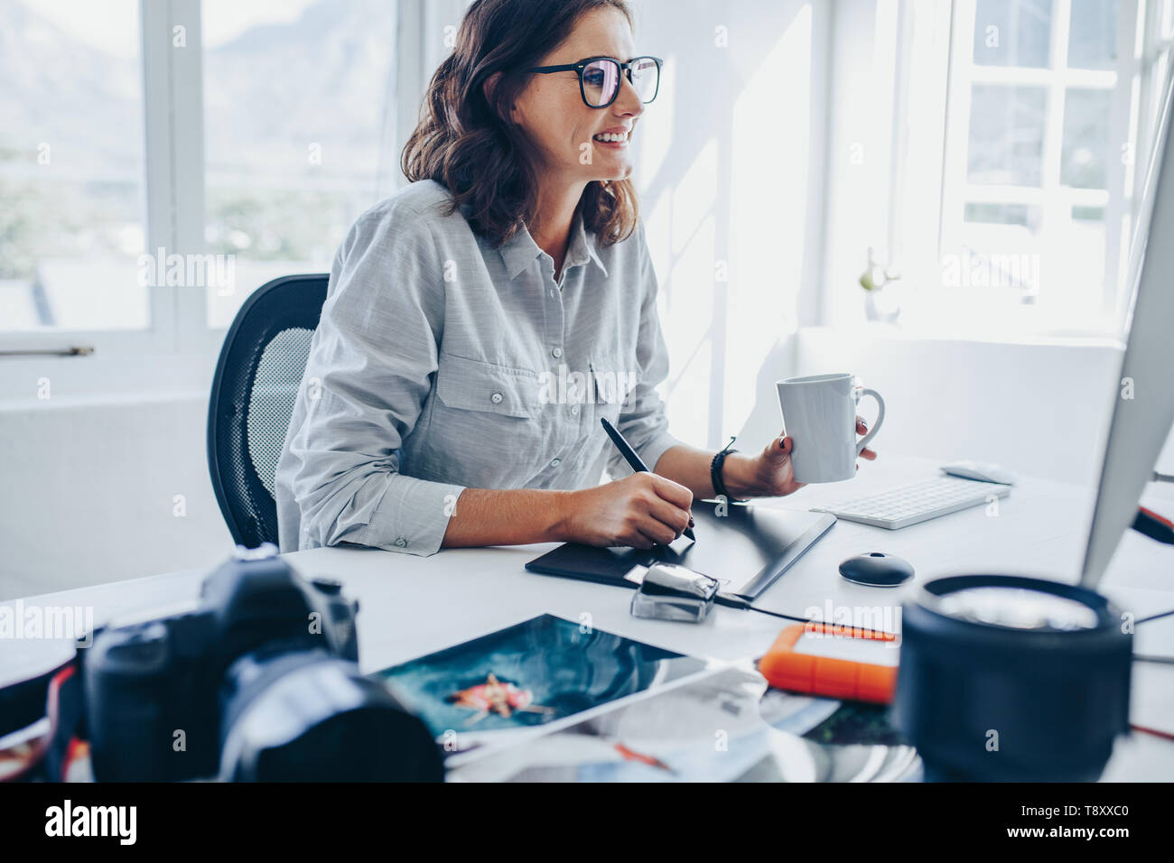 Young woman sitting at desk editing images on computer. Female photographer retouching photos in office using graphic tablet and digital pen. Stock Photo