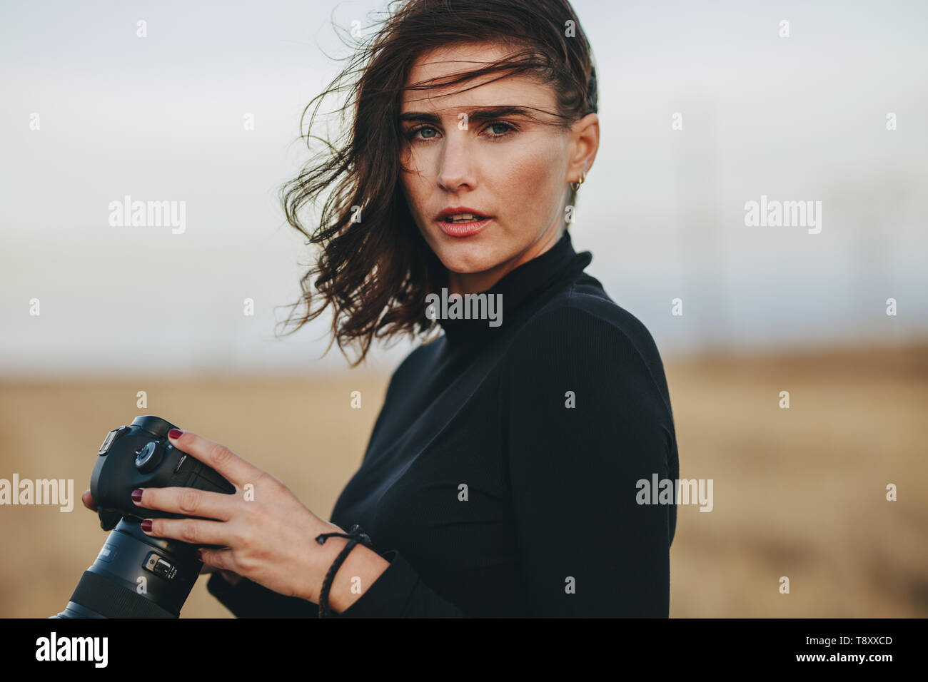 Professional Photographer During A Outdoors Photoshoot Young Woman In Casual Holding A Photo Camera Outdoors Stock Photo Alamy