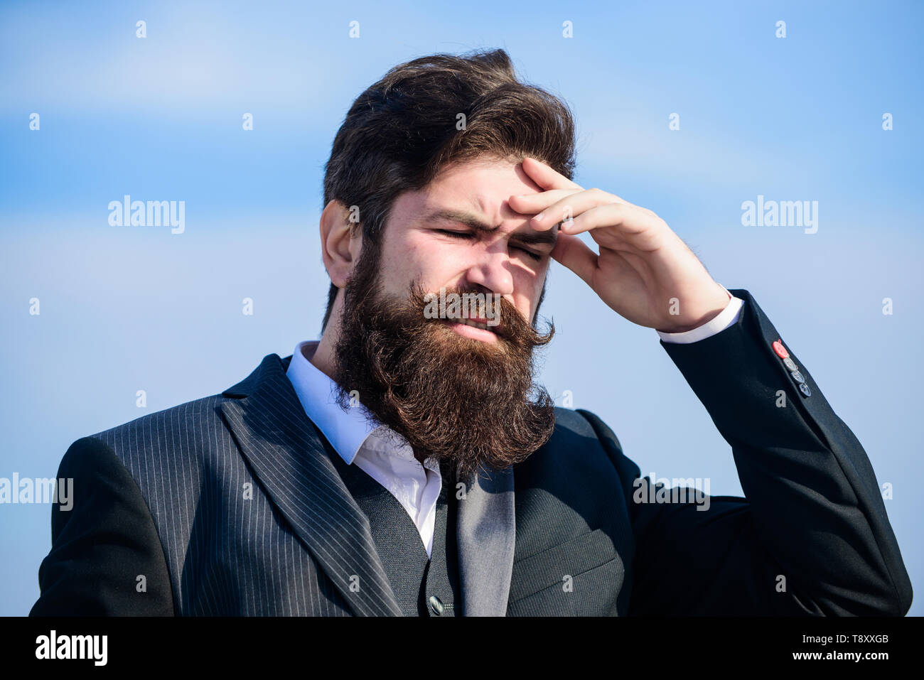 Guy suffer headache stressful day. Stressful business. Pain and migraine. Frustration and disappointment. Unforgivable mistake. Business failure. Man bearded stressful painful face sky background. - Stock Image