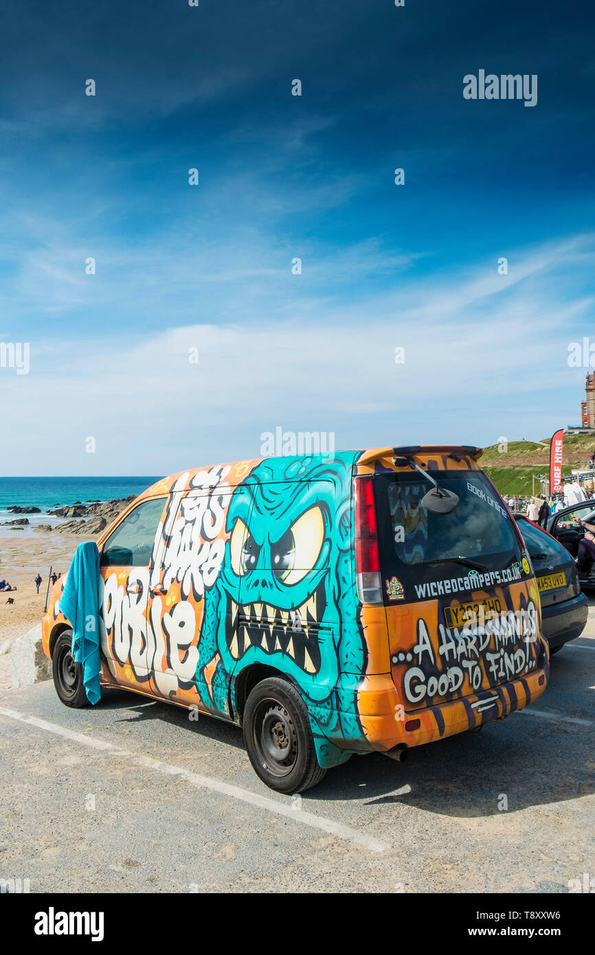 A highly decorated camper van parked overlooking Fistral Beach in Newquay in Cornwall. - Stock Image