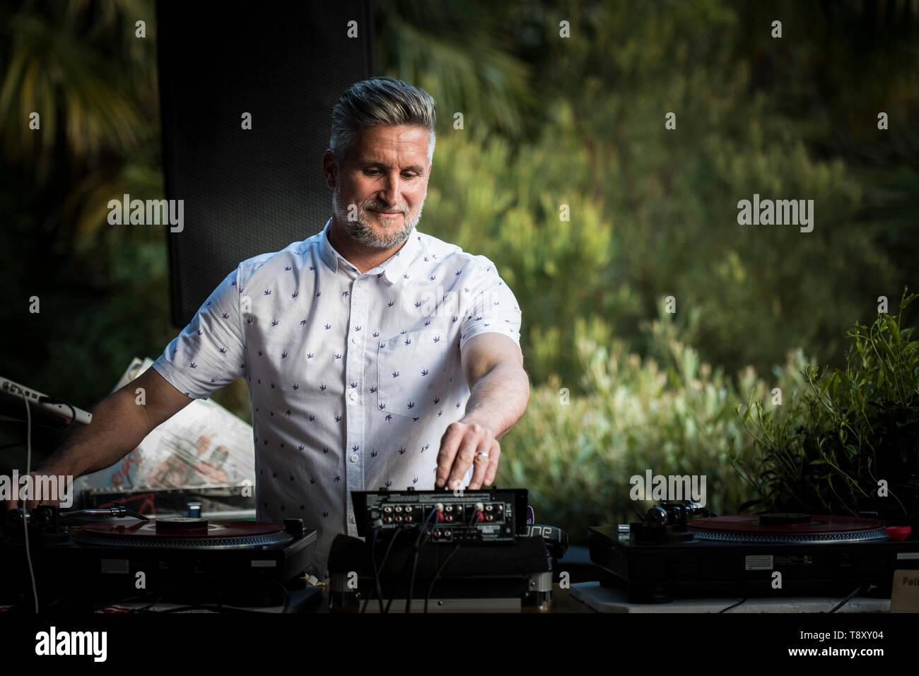 A DJ playing music at Trebah Garden in Cornwall. - Stock Image