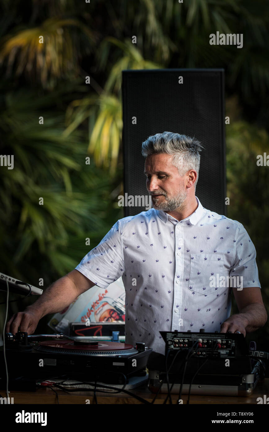 A DJ playing music at an event at Trebah Garden in Cornwall. - Stock Image