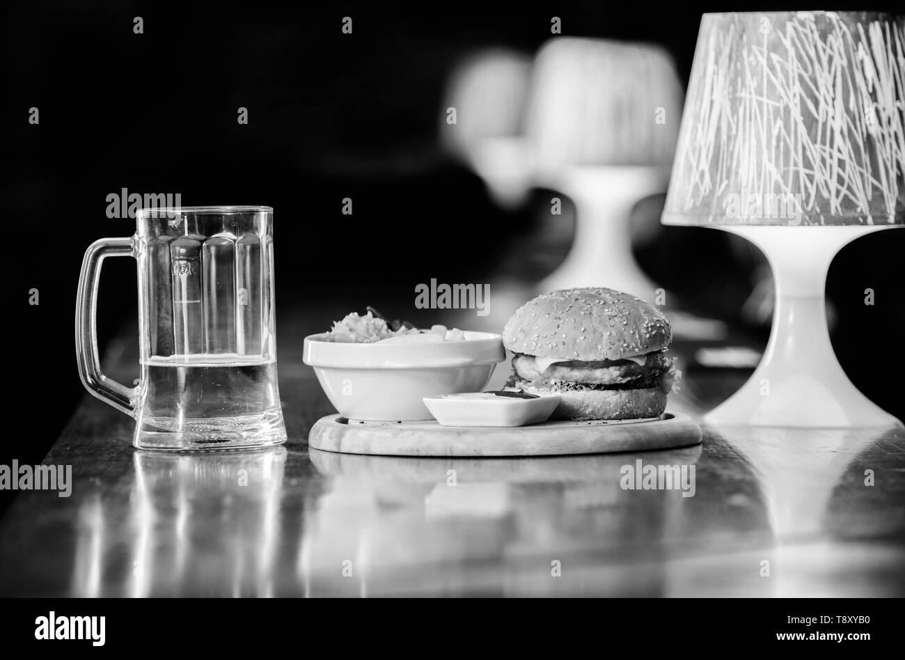 High calorie snack. Hamburger and french fries and tomato sauce on wooden board. Delicious burger. Burger with cheese meat and salad. Pub food and mug of beer. Fast food concept. Burger menu. - Stock Image