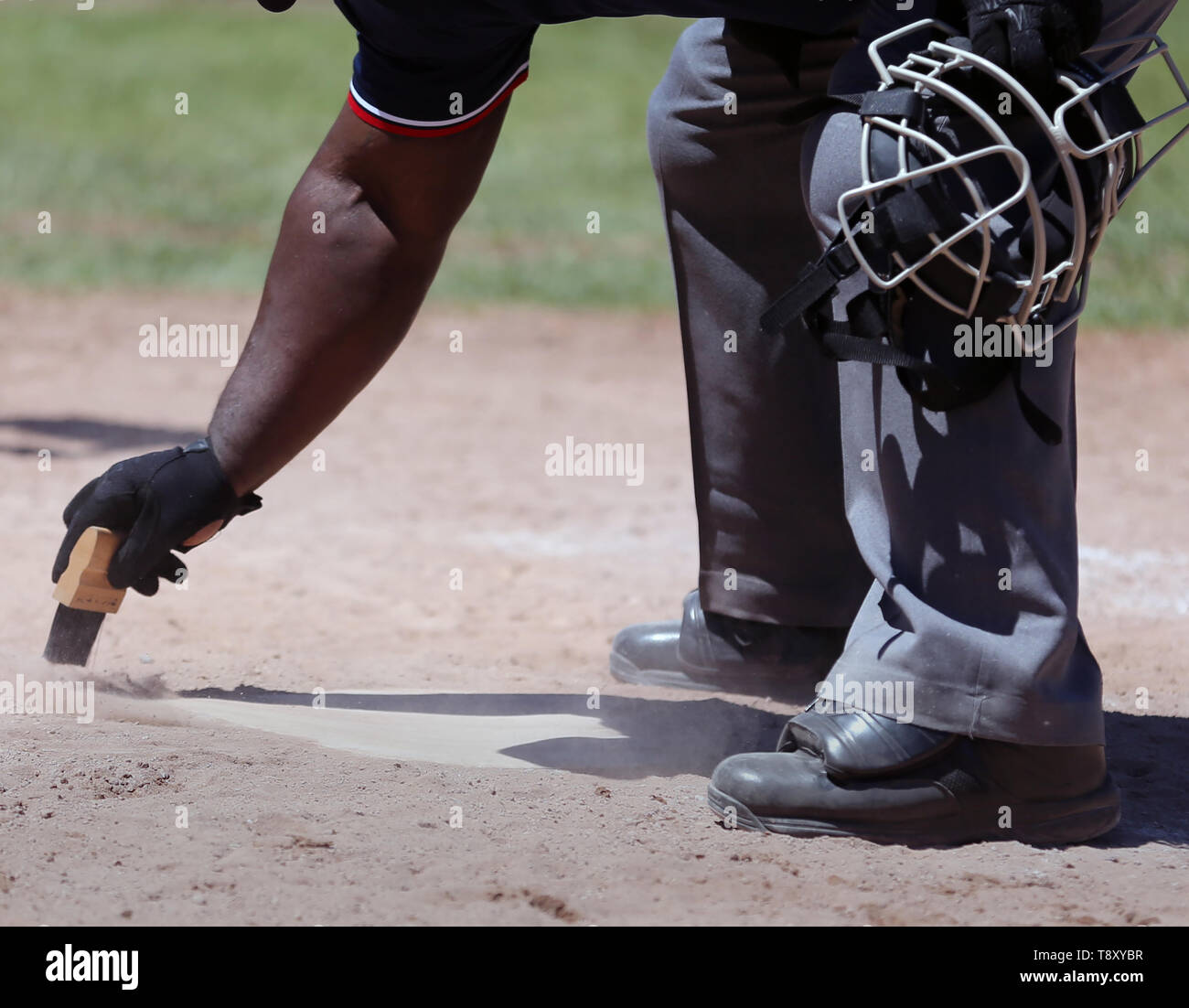 African American umpire cleaning home plate at a high school baseball game Stock Photo