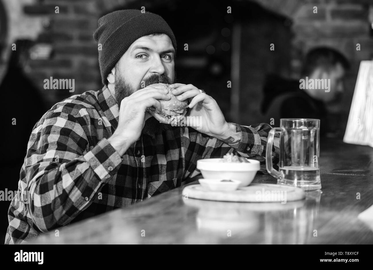 High calorie food. Delicious burger concept. Enjoy taste of fresh burger. Hipster hungry man eat burger. Man with beard eat burger menu. Brutal hipster bearded man sit at bar counter. Cheat meal. - Stock Image