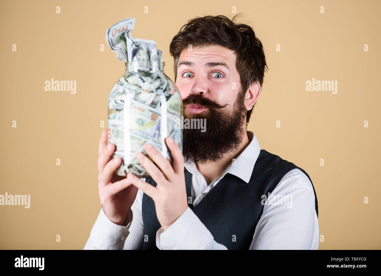Keeping money in saving bank. Bearded man holding glass jar with paper bank notes. My money going directly into the piggy bank. Bank and banking. Stock Photo