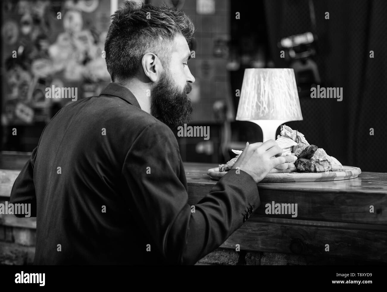 Enjoy meal. Restaurant client. Hipster formal suit sit at bar counter. Man received meal with fried potato fish sticks meat. Delicious meal. Cheat meal concept. Hipster hungry eat pub fried food. - Stock Image