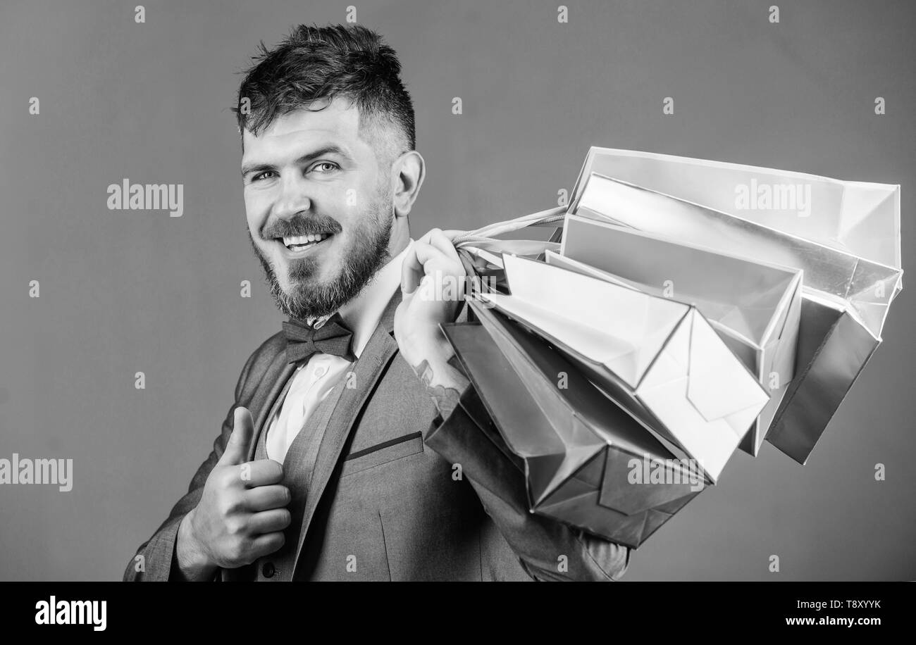 Elite boutique. Man bearded elegant businessman carry shopping bags on grey background. Make shopping more joyful. Enjoy shopping profitable deals black friday. Shopping with discount enjoy purchase. - Stock Image